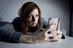Młoda smutna podatna dziewczyna używa telefon komórkowego i desperackiego cierpienia online nadużycie cyberbullying okaleczał zdjęcia royalty free