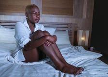 Młoda smutna przygnębiona czarna afro amerykańska kobieta w łóżkowy cierpienie depresji uczucia nędzny, chory patrzeć i zdjęcie royalty free