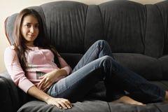 Młoda spokojna kobieta na kanapie Zdjęcie Royalty Free