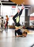 Młoda sportowa dziewczyna ubierał w sportswear robi handstand na podłodze w nowożytnym gym obrazy stock