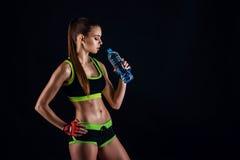 Młoda sportowa kobieta w sportswear z butelką w studiu przeciw czarnemu tłu Idealna kobieta sportów postać obraz royalty free
