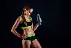 Młoda sportowa kobieta w sportswear z butelką w studiu przeciw czarnemu tłu Idealna kobieta sportów postać Sprawności fizycznej d zdjęcie royalty free