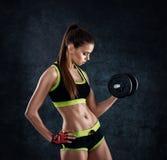 Młoda sportowa kobieta w sportswear z dumbbells w studiu przeciw ciemnemu tłu Idealna kobieta sportów postać Sprawności fizycznej zdjęcie royalty free