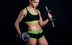 Młoda sportowa kobieta w sportswear z dumbbells w studiu przeciw czarnemu tłu Idealna kobieta sportów postać Sprawności fizycznej zdjęcia stock