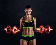 Młoda sportowa kobieta w sportswear z ognistymi dumbbells w studiu przeciw czarnemu tłu Idealna kobieta sportów postać obrazy royalty free