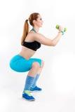 Młoda sportowa miedzianowłosa kobieta w jaskrawym sportswear robi kucnięciom Zdjęcia Royalty Free