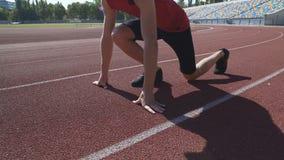 Młoda sportowiec pozycja wewnątrz kuca początek pozycję, przygotowywającą współzawodniczyć dla sukcesu zdjęcie wideo