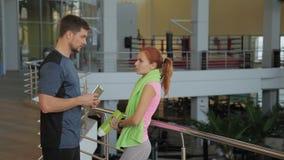 Młoda sportsmenka dyskutuje ona z jej osobistym trenerem w gym rezultaty zbiory wideo