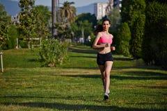 Młoda sporty dziewczyna w jaskrawym sportswear bieg w parku na pięknym drzewa tle Obrazy Royalty Free