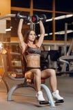 Młoda sporty kobieta robi ćwiczeniom z dumbbells dla ramion na ławce w gym obrazy royalty free