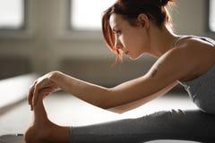 Młoda sporty kobieta robi joga rozciąga ćwiczenia obsiadanie w gym blisko jaskrawych okno obraz stock