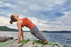 Młoda sporty kobieta robi różnym wariantom joga pozycja na skalistym rivershore Fotografia Stock