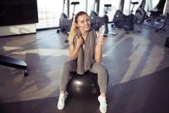 Młoda sporty kobieta w gym mienia butelce z świeżą wodą Fotografia Royalty Free