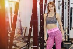 Młoda sprawności fizycznej dziewczyna w gym między symulantami obrazy royalty free