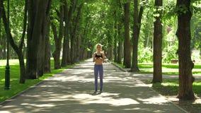 Młoda sprawności fizycznej dziewczyna w spodniach biega przez parka zbiory wideo