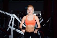 Młoda sprawności fizycznej kobieta demonstruje skrzyżowań ćwiczenia Piersiowi mięśnie, ciężki szkolenie z maszyna kablem Zdjęcia Stock