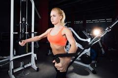 Młoda sprawności fizycznej kobieta demonstruje skrzyżowań ćwiczenia Piersiowi mięśnie, ciężki szkolenie z maszyna kablem Obrazy Royalty Free