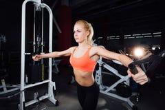 Młoda sprawności fizycznej kobieta demonstruje skrzyżowań ćwiczenia Piersiowi mięśnie, ciężki szkolenie z maszyna kablem Fotografia Stock