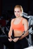 Młoda sprawności fizycznej kobieta demonstruje skrzyżowań ćwiczenia Piersiowi mięśnie, ciężki szkolenie z maszyna kablem Zdjęcie Stock