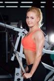 Młoda sprawności fizycznej kobieta demonstruje skrzyżowań ćwiczenia Piersiowi mięśnie, ciężki szkolenie z maszyna kablem Obraz Royalty Free