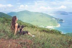 Młoda sprawności fizycznej kobieta odpoczywa lub biega w sportswear siedzieć na trawiastym halnym szczycie i patrzeć morze po ćwi zdjęcie royalty free