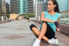 Młoda sprawności fizycznej kobieta odpoczywa po ćwiczyć, siedzący przy ławką w centrum miasta obrazy stock