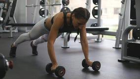 Młoda sprawności fizycznej kobieta robi dumbbell wiosłuje przy crossfit gym Sportive dziewczyna ćwiczy - ciągnienie ciężar piękna Zdjęcia Stock