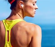 Młoda sprawności fizycznej kobieta słucha muzyka przy bulwarem zdjęcia stock
