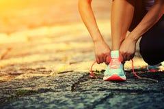Młoda sprawności fizycznej kobieta wiąże shoelaces Zdjęcie Royalty Free
