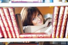 Młoda studencka dziewczyna przy książkową półką fotografia stock