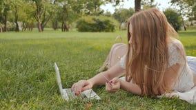 Młoda studencka dziewczyna robi zapłatom z kredytową kartą na trawie w miasto parku laptopem i podczas gdy kłamający zdjęcie wideo