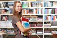 Młoda studencka dziewczyna z książkami w bibliotece Zdjęcie Stock