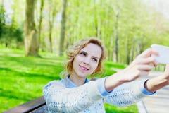 Młoda studencka uśmiechnięta dziewczyna bierze selfie fotografię na smartphone kamerze plenerowej, piękny bokeh tło, nastoletni t zdjęcie stock