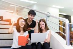Młoda Studenckiej grupy Czytelnicza książka i Używać laptopu uśmiech fotografia royalty free