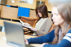 Żeńskiego ucznia dziewczyna z książką w bibliotece Obrazy Stock