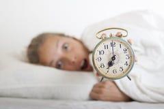 Młoda sypialna kobieta i budzik w łóżku Fotografia Royalty Free