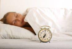 Młoda sypialna kobieta i budzik w łóżku Obrazy Royalty Free