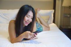 Młoda szczęśliwa ładna Azjatycka Koreańska kobieta lub pokoju hotelowego lying on the beach na łóżku w domu relaksowaliśmy uśmiec obrazy royalty free