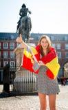 Młoda szczęśliwa atrakcyjna wekslowego ucznia dziewczyna ma zabawę w grodzkim odwiedza Madryt mieście pokazuje Hiszpania flaga Fotografia Stock