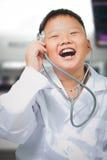 Młoda szczęśliwa azjatykcia chłopiec bawić się lekarkę obrazy royalty free