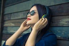 Młoda szczęśliwa azjatykcia kobieta używa hełmofon słuchać jej muzyka obrazy stock
