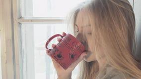 Młoda szczęśliwa blondynka używa smartphone komunikuje z chłopaka obsiadaniem na okno Jaskrawa uśmiechnięta młoda kobieta jest zbiory