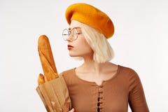 Młoda szczęśliwa blondynki dama w żółtej bereta uściśnięcia paczce z baguettes i cieszy się one odizolowywamy nad białym tłem w s zdjęcie stock