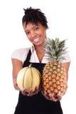 Młoda szczęśliwa czerni, amerykanina afrykańskiego pochodzenia kobieta sprzedaje świeże owoc/ Zdjęcie Royalty Free