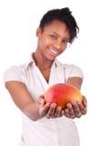 Młoda szczęśliwa czerni, amerykanina afrykańskiego pochodzenia kobieta trzyma świeżego mango/ Zdjęcie Royalty Free