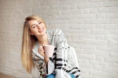 Młoda szczęśliwa dziewczyna zawijająca w ciepłej koc patrzeje szczęśliwą trzymający filiżankę herbata indoors zdjęcia stock