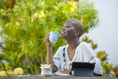 Młoda szczęśliwa i atrakcyjna czarna afro Amerykańska kobieta pracuje z pastylką outdoors przy kawiarnią relaksował pić herbaty l Obrazy Stock