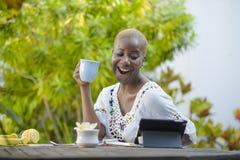 Młoda szczęśliwa i atrakcyjna czarna afro Amerykańska kobieta pracuje z pastylką outdoors przy kawiarnią relaksował pić herbaty l Obraz Stock