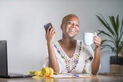Młoda szczęśliwa i atrakcyjna czarna afro amerykańska modniś kobieta pracuje w domu biuro z laptopem na wiszącej ozdobie używać i zdjęcia stock