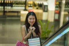 Młoda szczęśliwa i piękna Azjatycka Koreańska kobieta przy centrum handlowe eskalatoru przewożenia torba na zakupy w centrum hand fotografia stock